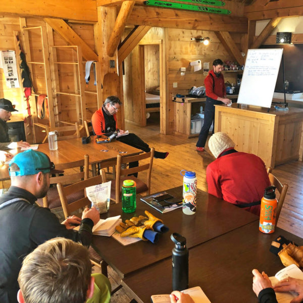 A group of students take notes during an avalanche lesson on an AIARE 1 course at the Broome Hut in Colorado.