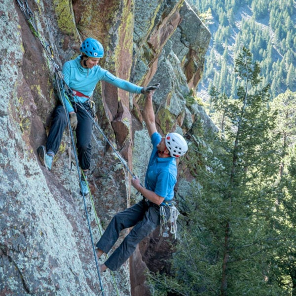 AMGA Certified Rock Guide, Madaleine Sorkin, gives a climber a high five at the top of a route during a Mad Sensei Climbing Camp.