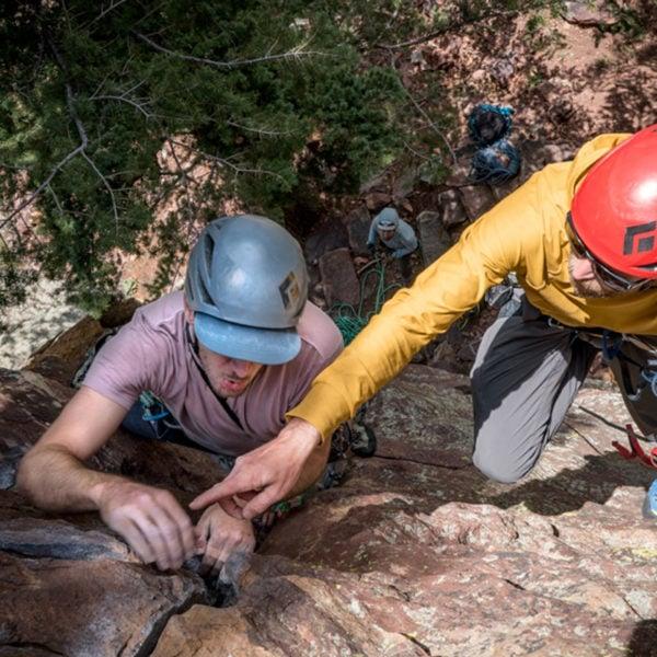 Justen Sjong instructs a rock climber on a climb in Eldorado Canyon State Park, Colorado.