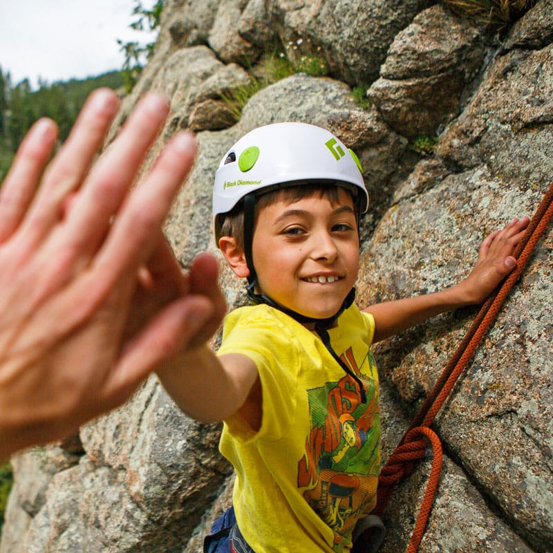 Young rock climber giving a high-five.