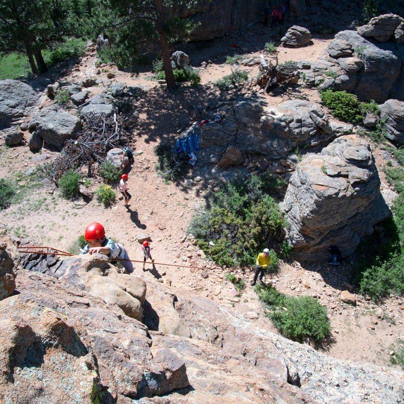 A group of rock climbers participate in a group rock climbing activity in Estes Park, Colorado.