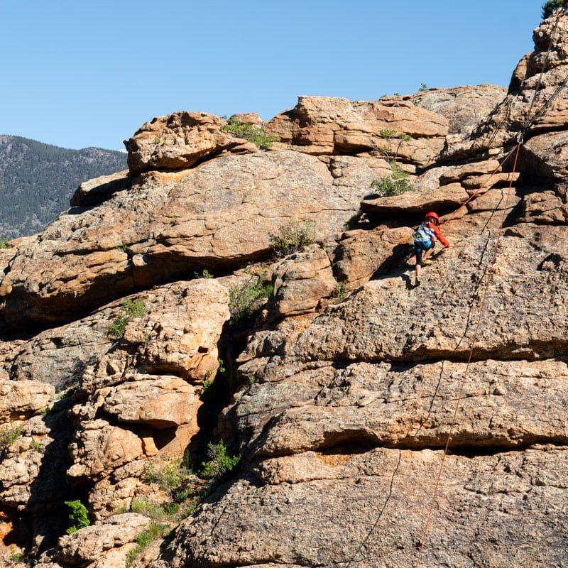 A young adventurer tries rock climbing while on vacation in Estes Park, Colorado.