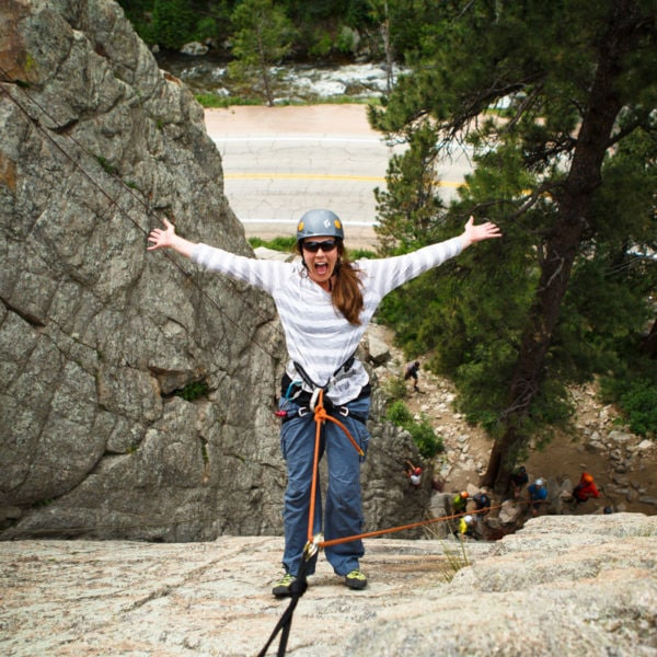 A particpant on a Half Day Fun Rock Climbing Excursion leans back on the rope with her hands in the air.