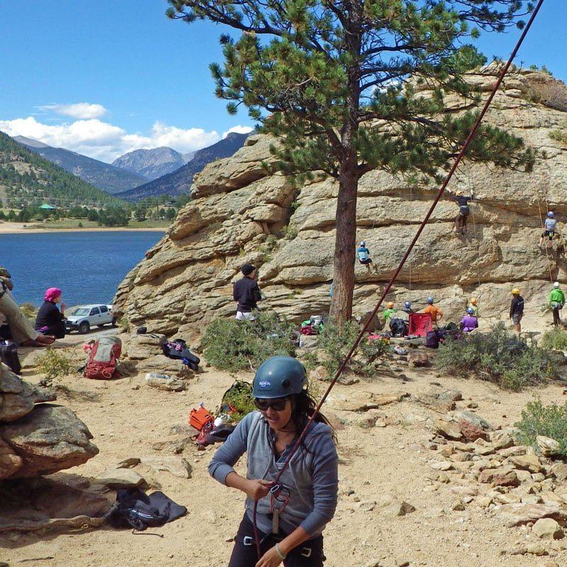 A group of beginner rock climbers having fun in the sun on a Half Day Fun Climb at Mary's Lake in Estes Park, Colorado.