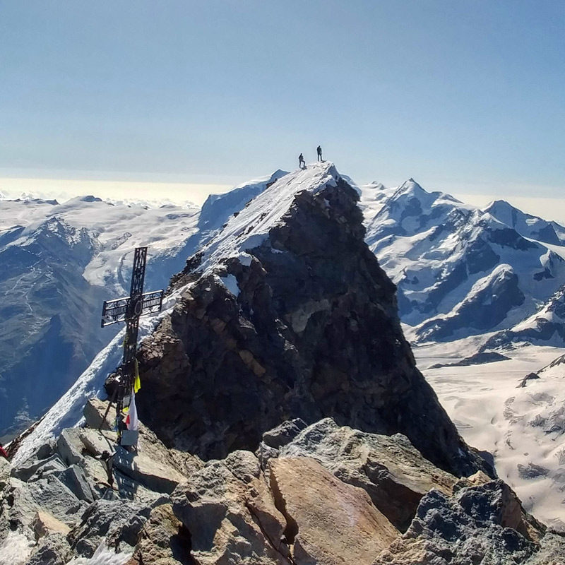 A guided party of climbers stand on the summit of The Matterhorn.