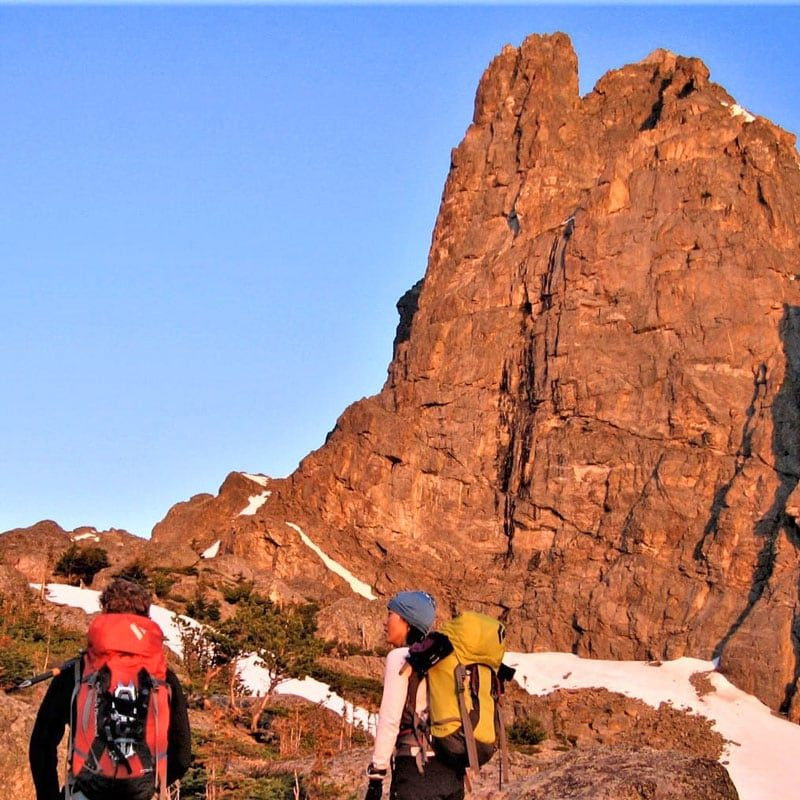 A pair of mountaineers stand below Notchtop Spire in the early morning sunrise in Rocky Mountain National Park.