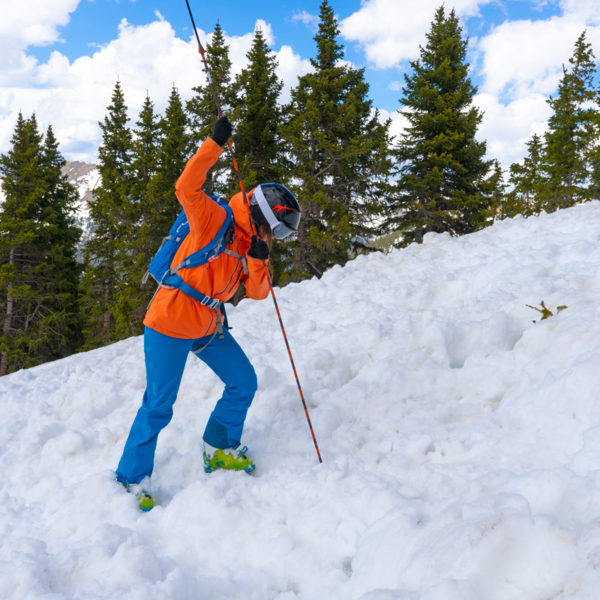 A student on an AIARE Avalanche Rescue Course probes for victims on a snow slope covered in avalanche debris.