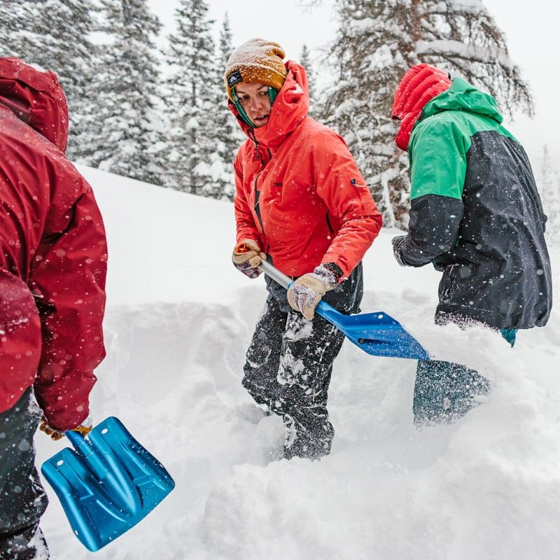 A group of backcountry skiers and splitboarders dig snow during an avalanche training drill on an AIARE Avalanche Rescue course in Colorado.