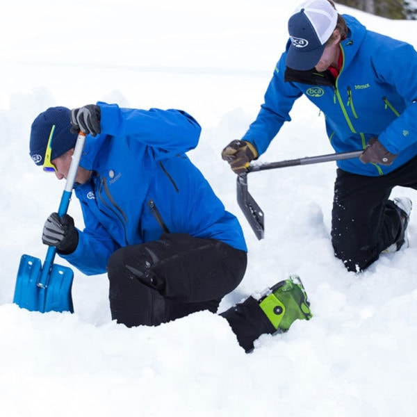 A pair of students practice an avalanche rescue scenario during an AIARE avalanche rescue course near Denver, Colorado.