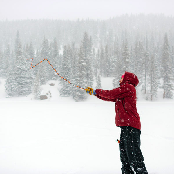 A backcountry skier deploys an avalanche probe during companion rescue lesson near Vail Pass, Colorado.