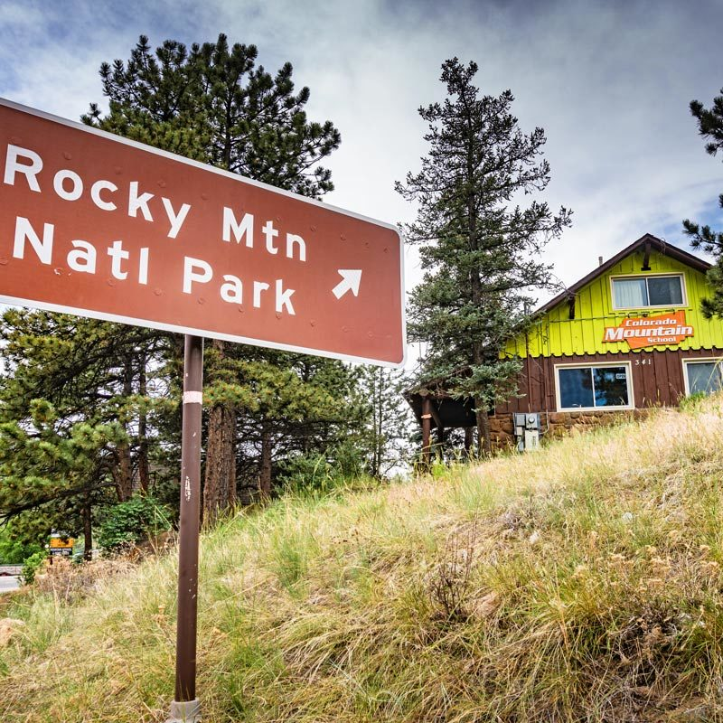 """The """"Rocky Mountain National Park"""" street sign stands outside the Estes Park Adventure Hostel."""