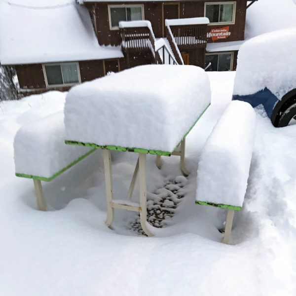 16 inches of snow stands on a picnic table outside the Estes Park Adventure Hostel.