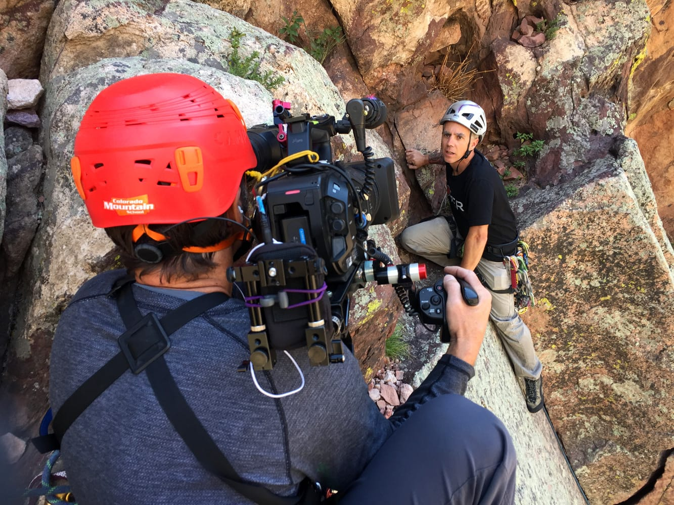 Videographer films a rock climber in Eldorado Canyon, near Boulder Colorado. Colorado Mountain School Guide stands back after safely rigging technical rope systems for the film shoot.