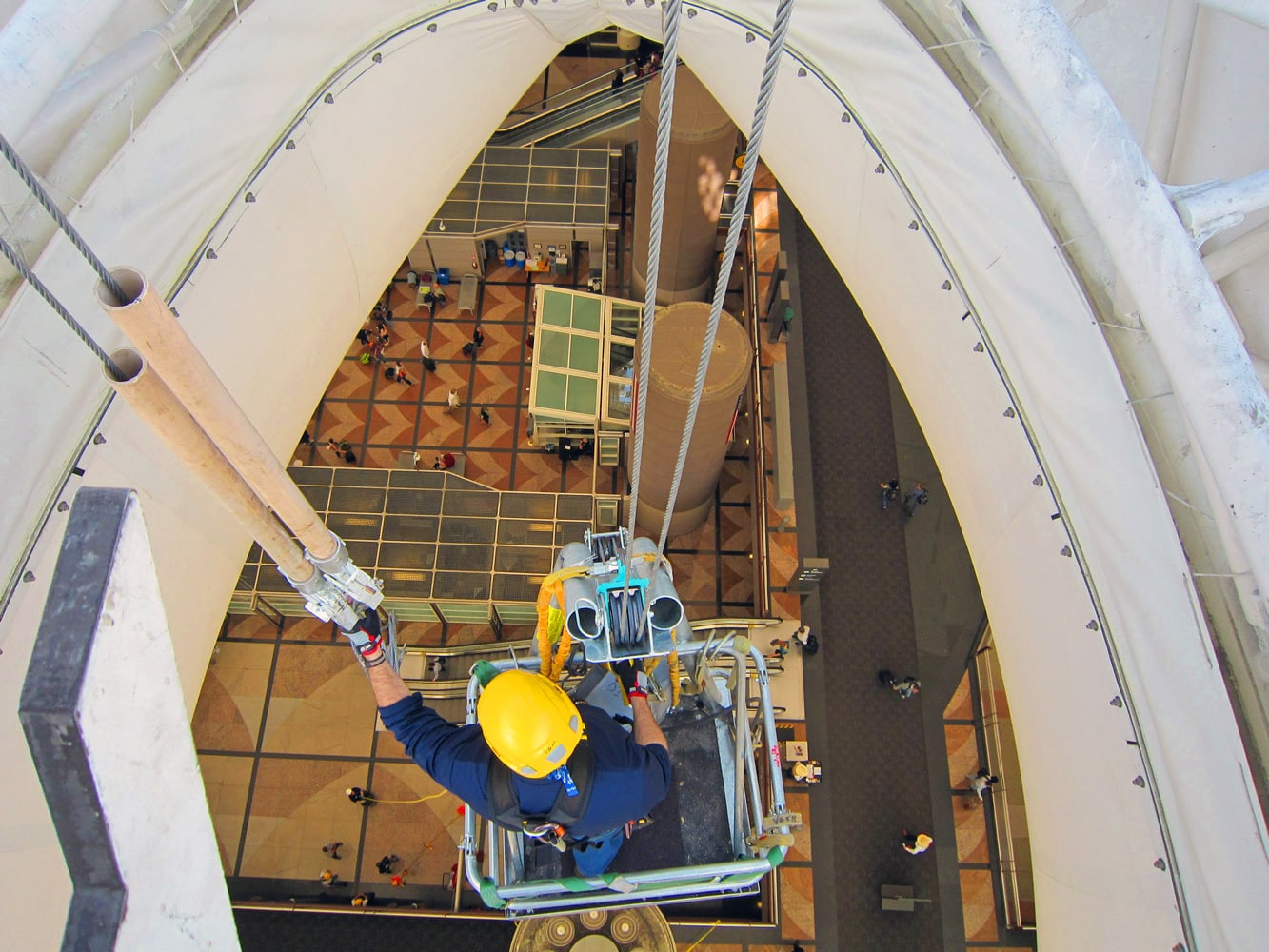 High rope maintenance member makes repairs to the roof at Denver International Airport under the close supervision of Colorado Mountain School Guide. CMS Guides often assist with industrial, film and entertainment rigging services.