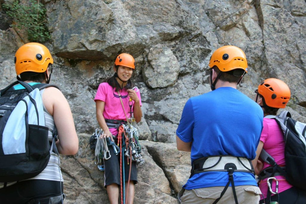 Colorado Mountain School guide Norie Kizaki teaches rock climbers on a lead climbing course.