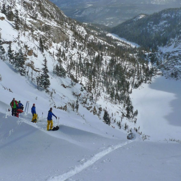 Backcountry skiiers prepare to drop in on a snowy slope during a guided ski tour of Rocky Mountain National Park.