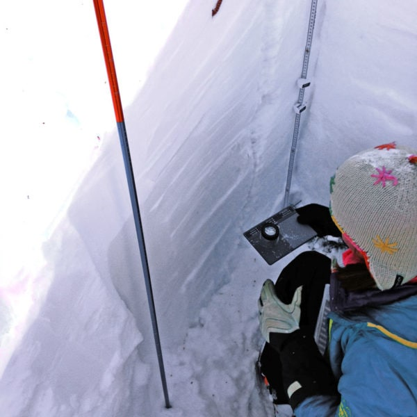 A student on an AIARE Level 2 avalanche training course uses a snow study kit to analyze snow crystals.
