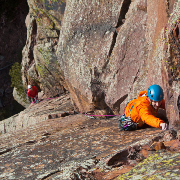 Leader placing protection on a multi-pitch climb while the belayer looks up from below.