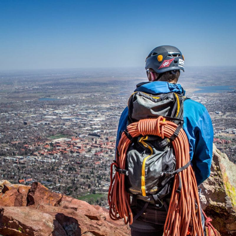 A rock climber, wearing a backpack and coiled rope, stands on the summit of the First Flatiron, overlooking Boulder, Colorado.