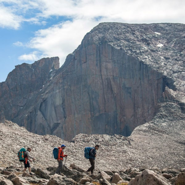 Three mountaineers hike across The Boulderfield with East Face of Longs Peak in the background.