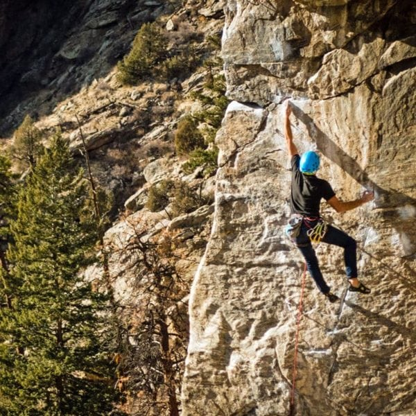 A sport climber reaches for a large hold near the end of a route in Clear Creek Canyon - just outside of Denver, Colorado.