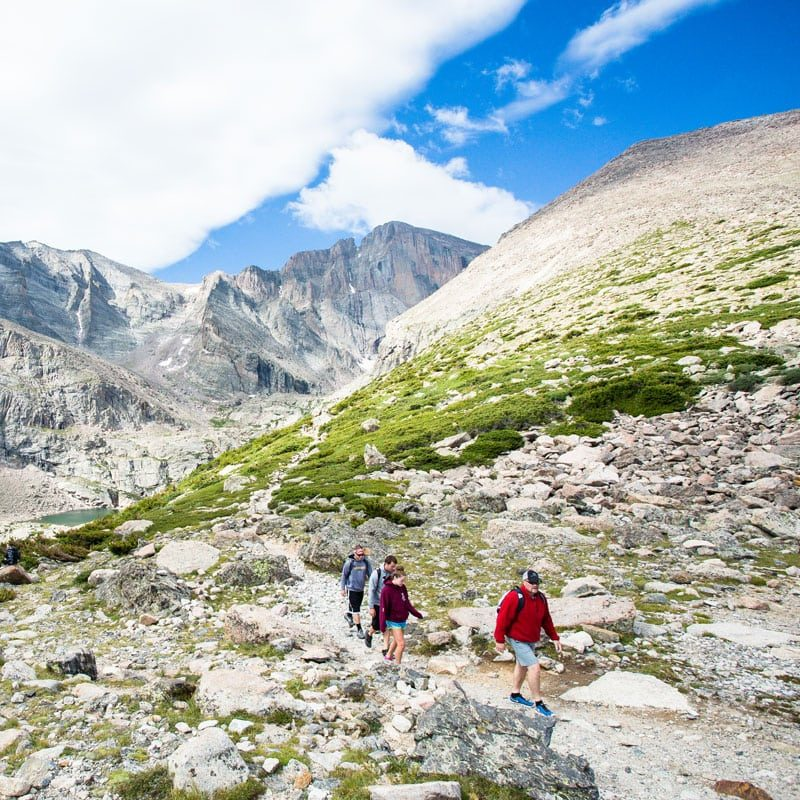 A group of hikers pass through Chasm Junction after having hiked to Chasm Lake in Rocky Mountain National Park.