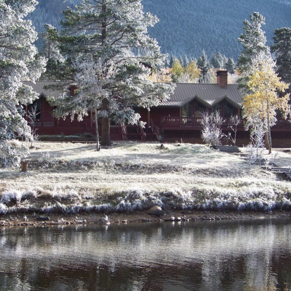 Dao House is covered with a fresh blanket of snow on a cold winter morning in Estes Park, Colorado. Doa House is an adventure basecamp for climbing Longs Peak.