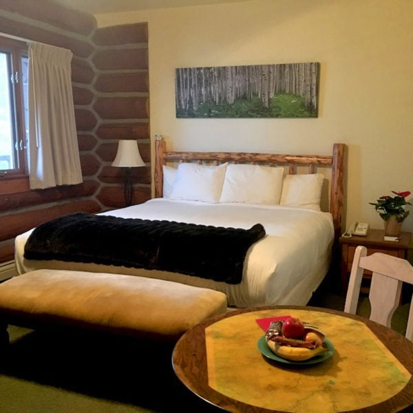 A bed sits near an open window at Dao House - an adventure lodge near Longs Peak in Estes Park, Colorado.