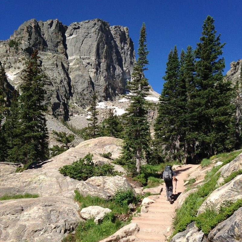 A climber approaches Hallet Peak via the Emerald Lake trail in Rocky Mountain National Park. Hallet Peak looms large in the background.