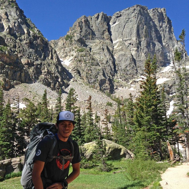 A rock climber poses in front of Hallet Peak in Rocky Mountain National Park.