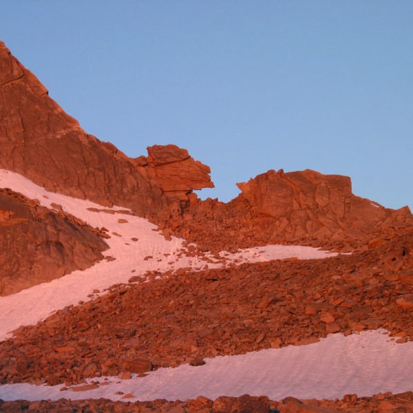 The Keyhole feature on Longs Peak is lit up by alpenglow.