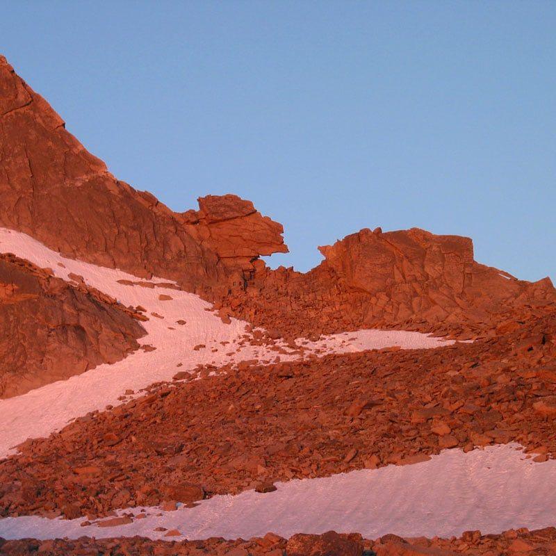 The Keyhole feature on Longs Peak is lit up by alpenglow.