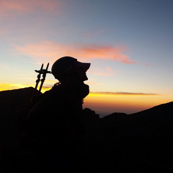 A mountaineer on The Keyhole route on Longs Peak, looks toward the summit - silhouetted by the morning sunrise.