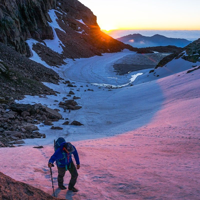 A climber ascends Lambs Slide at sunrise. This section begins the technical climbing on Kieners route.