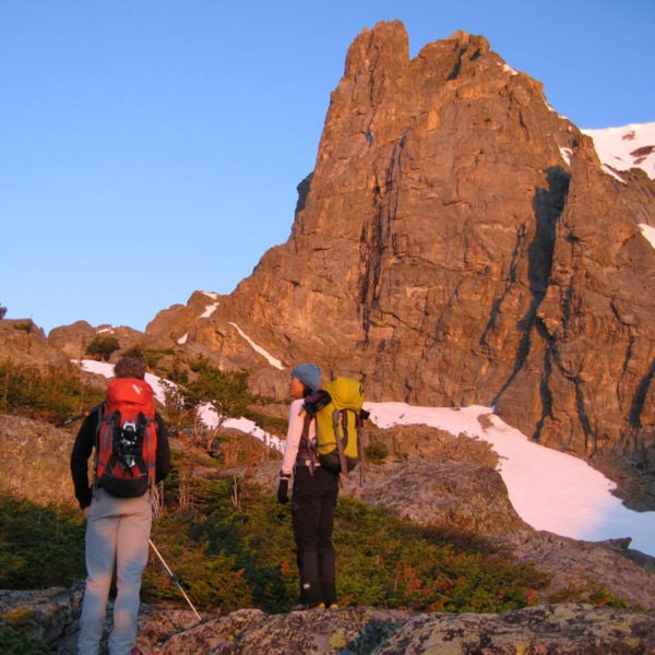 A pair of rock climbers look toward Notchtop Mountain at sunrise in Rocky Mountain National Park.