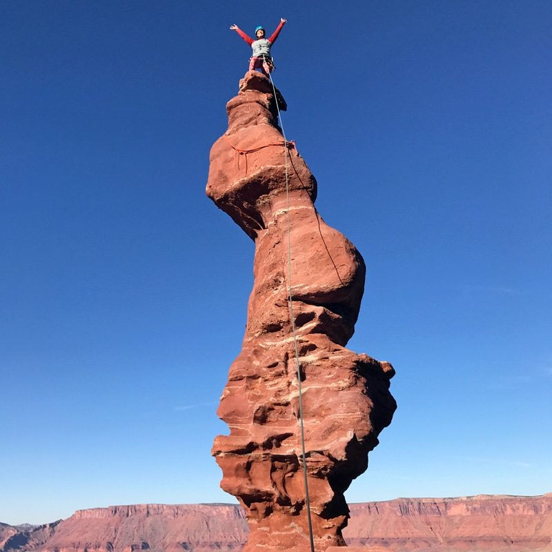 A happy rock climber stands on the summit of Ancient Art - one of Moab's classic climbs.