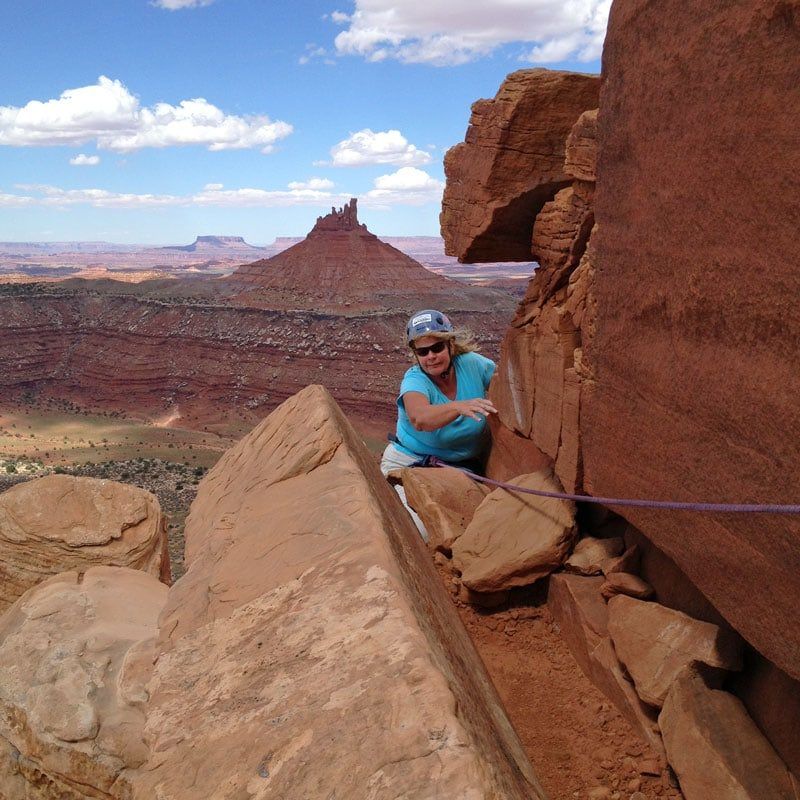 A rock climber turns the corner on a Moab Classic Climb with Colorado Mountain School.