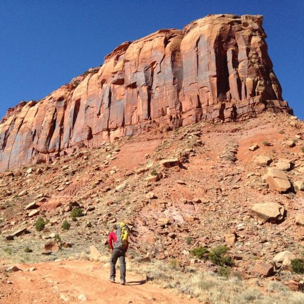A rock climbing guide hikes down a trail on a guided climb at Indian Creek near Moab, Utah.