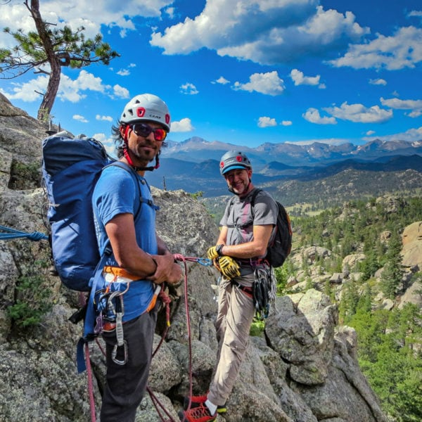 A pair of rock climbers stand on a ledge during a guided rock climb at Lumpy Ridge with Estes Park in the background.