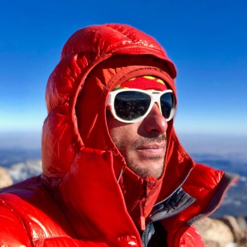 Colorado Mountain School Guide, Max Lurie, looks off at the horizon from the top of a mountian.