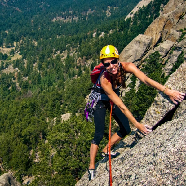 A rock climber smiles for the camera high on a route at Lumpy Ridge in Rocky Mountain National Park.