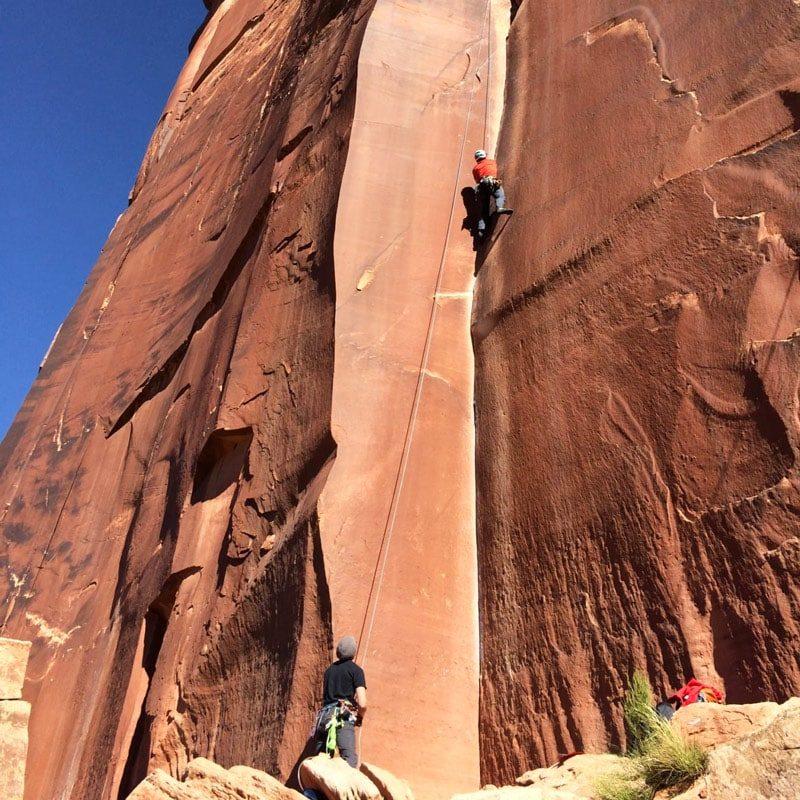 A rock climber top ropes a splitter crack climb at Indian Creek.