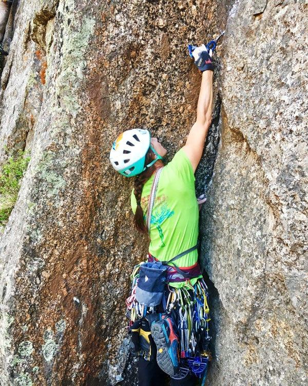 Colorado Mountain School Guide, Sarah Janin, places a piece of protection while leading a rock climb.
