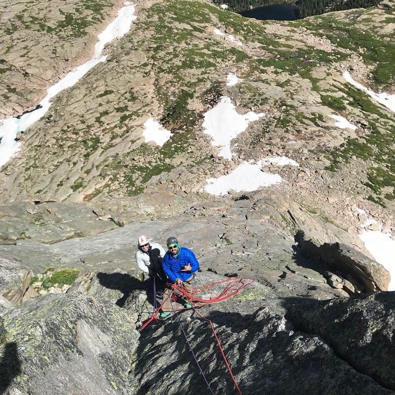 A pair of climbers stand at a belay ledge midway up The North Ridge, Spearhead, RMNP.