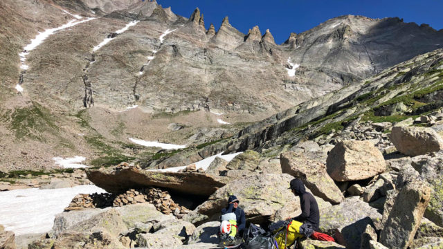 A pair of rock climbers sit at the Spearhead Bivy Sites in Glacier Gorge, Rocky Mountain National Park. Longs Peak and the Keyboard of the Winds tower high above.
