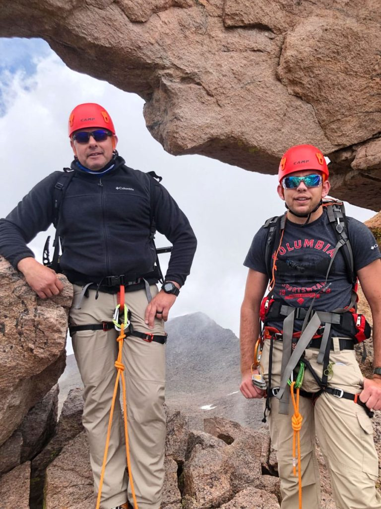 A pair of climbers, pass through The Keyhole on Longs Peak. The men are wearing harness, helmet and are roped up in preparation for the more exposed sections of climbing on Longs Peak - from The Keyhole to The Homestretch.