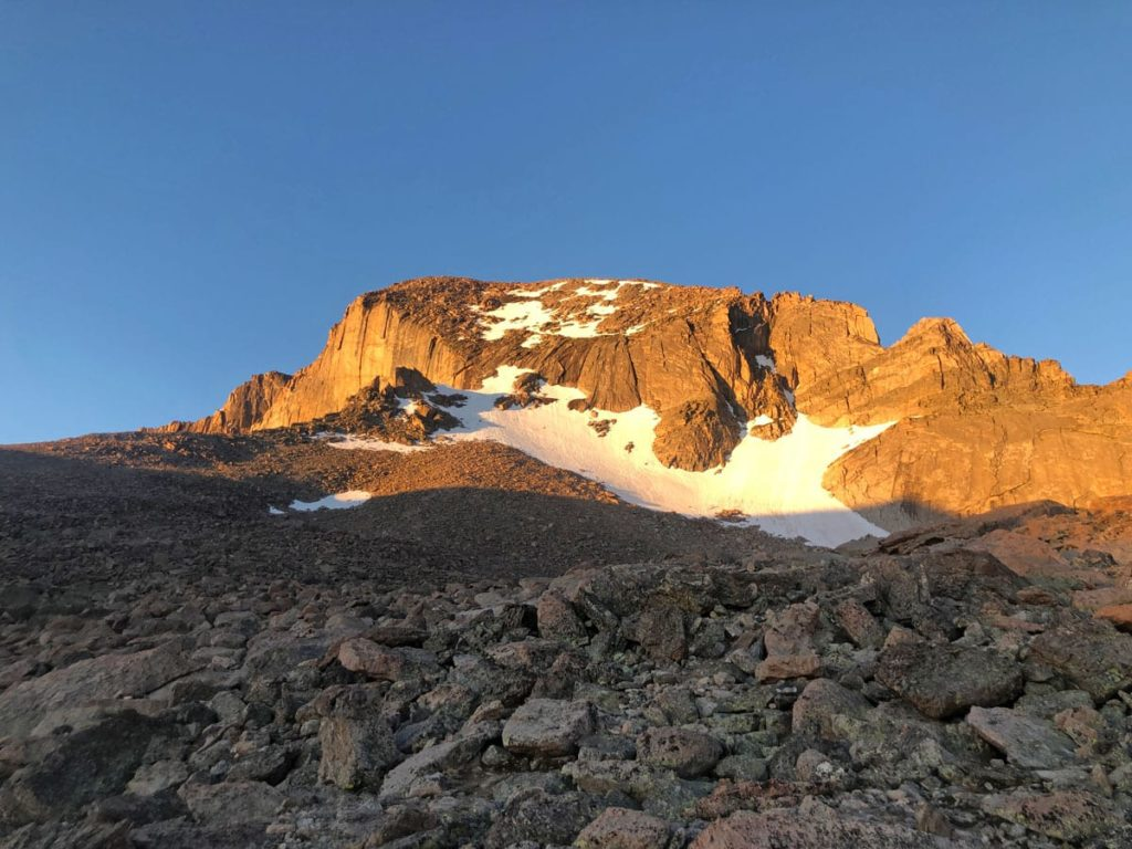 A view of The North Face of Longs Peak at sunrise. The Keyhole Route passes through The Boulderfield (seen here), then trends right, through The Keyhole itself.