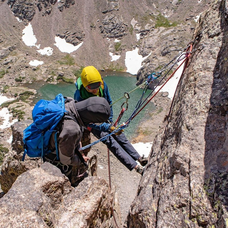 A pair of rock climbers prepare to descend Petit Grepon via the rappel route after summiting spire via the South Face route.