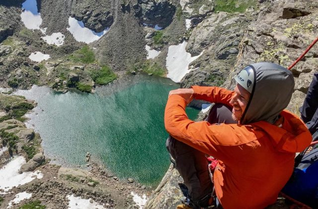 Clint Locks, Colorado Mountain School Guide, looks out over Sky Pond from high on the Petit Grepon's South Face.