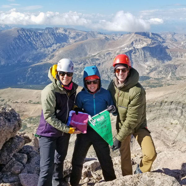 A team of climbers stand on the summit of Longs Peak in Colorado. They are participating in an adventure fundraising climb to raise money for charity.